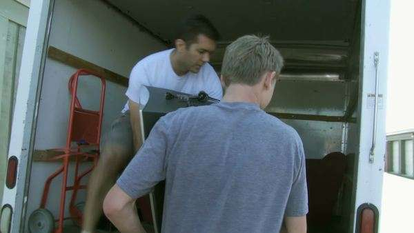 Man and teenager load a large television into a van as they move furniture for an apartment.  Hand held camera. Royalty-free stock video