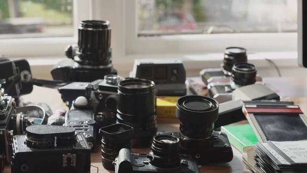 Dolly shot of multiple film cameras arranged on table and man choosing one Royalty-free stock video