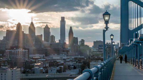 Medium wide shot of the sun setting behind the Philadelphia skyline. Shot from the Ben Franklin Bridge. Royalty-free stock video
