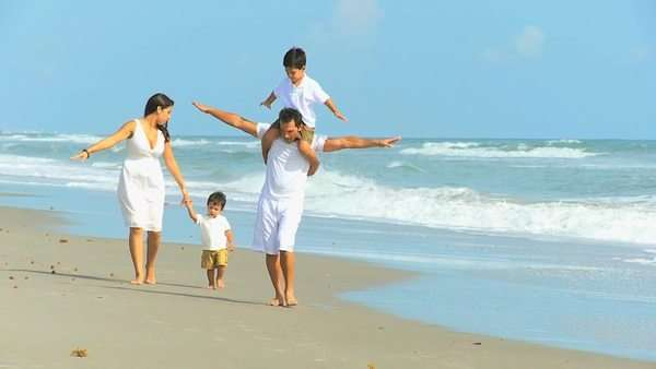 Latin American happy parents playing cute young sons by ocean shallows outing to beach Royalty-free stock video