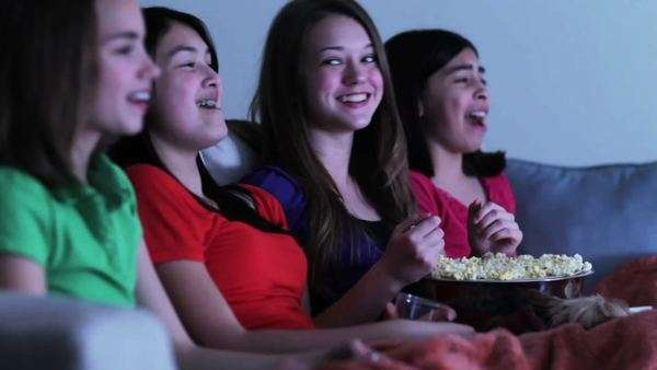 Four girls on sofa eating popcorn watching funny movie Royalty-free stock video