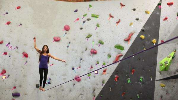 Mixed race girl walking on slackline at indoor climbing gym Royalty-free stock video