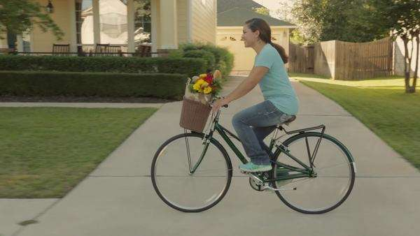 Hispanic woman riding bicycle with groceries through neighborhood Royalty-free stock video