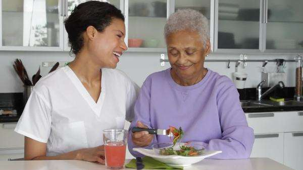 Senior woman with caregiver eating salad Royalty-free stock video