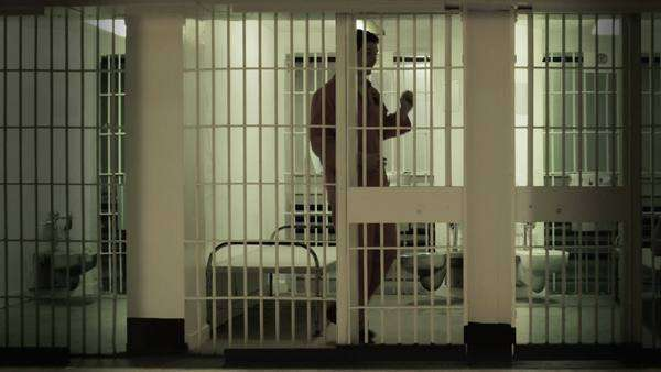 Inmate looking around from the bars of his prison cell Royalty-free stock video