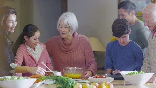 Three generations of happy family preparing a meal together in the kitchen at home Royalty-free stock video