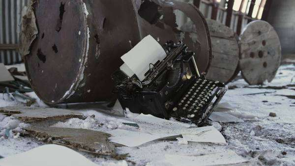 Tracking shot of typewriter lying in a snowy warehouse Royalty-free stock video