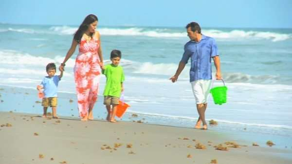 Latin American happy parents walking cute young sons by ocean shallows outing to beach carrying sand buckets Royalty-free stock video