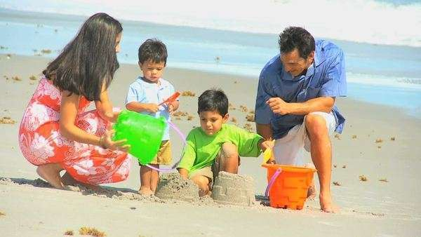 Young Hispanic parents dressed colorful casual clothes spending vacation playing beach buckets by ocean pre school sons. Royalty-free stock video