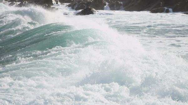 Powerful tidal waves crashing onto jagged rocks coastal waters slow motion shot on RED EPIC. Royalty-free stock video