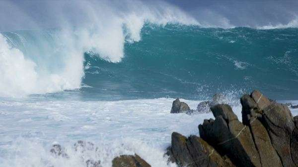 Powerful rolling surf crashing onto jagged rocks coastal waters slow motion shot on RED EPIC. Royalty-free stock video