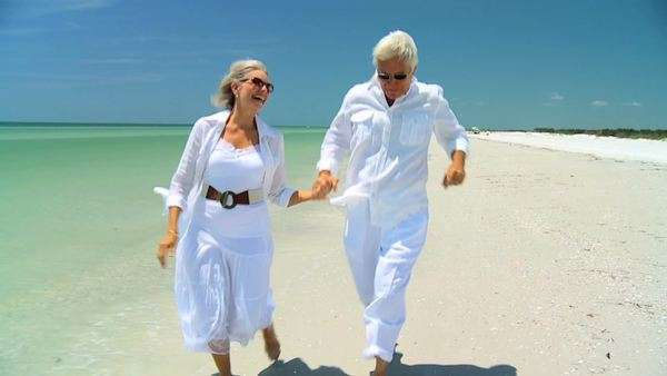 Attractive senior carefree couple running along the beach barefoot enjoying a fun lifestyle 60FPS. Royalty-free stock video