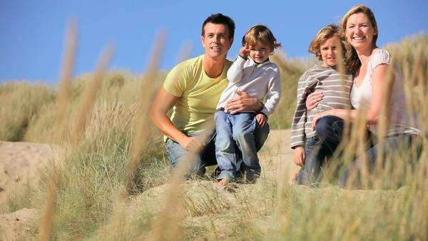 Attractive healthy young Caucasian family enjoying leisure time together outdoors on coastal sand dunes. Royalty-free stock video