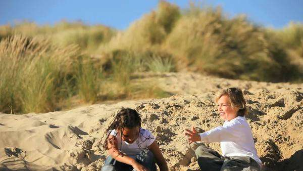 Mixed race childhood friends having healthy outdoor fun playing in sand dunes by the coast. Royalty-free stock video