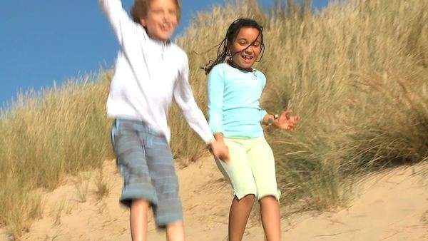 Mixed race childhood friends having fun playing in sand dunes by the coast filmed at 60fps. Royalty-free stock video