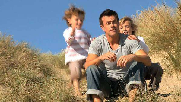 Young Caucasian father with his young sons spending time together by the coast. Royalty-free stock video
