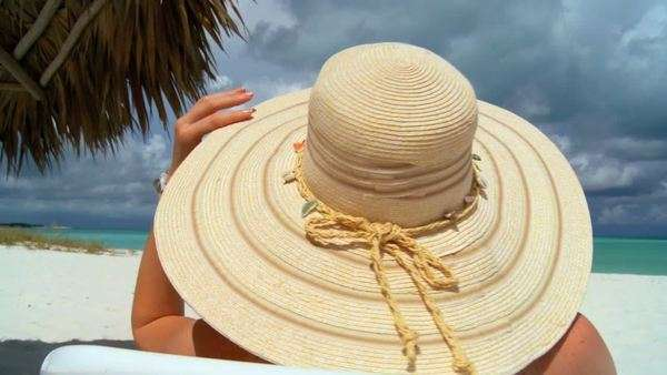 A woman with a straw hat surveys an ocean horizon from a tropical beach. Royalty-free stock video