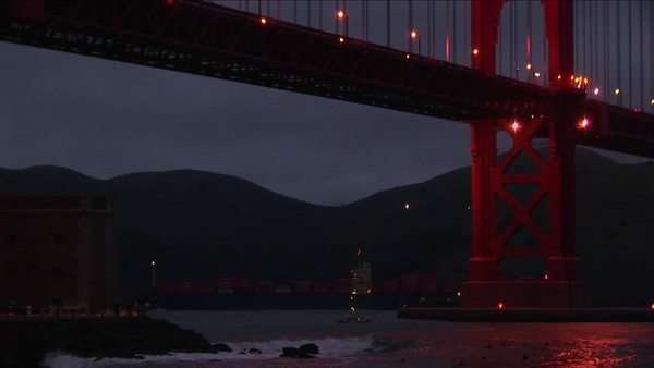Small boats passing under the Golden Gate Bridge at night are dwarfed by the enormous structure. Royalty-free stock video