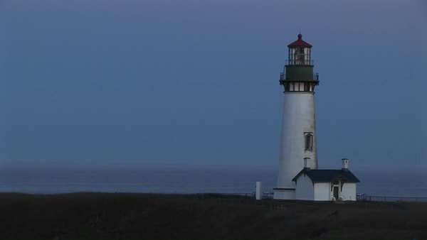 A beautiful blue sky is the perfect backdrop for this white lighthouse and the keeper's home. Royalty-free stock video