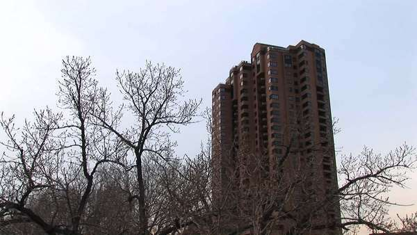A residential high-rise is shown in winter with bare trees in the foreground. Royalty-free stock video