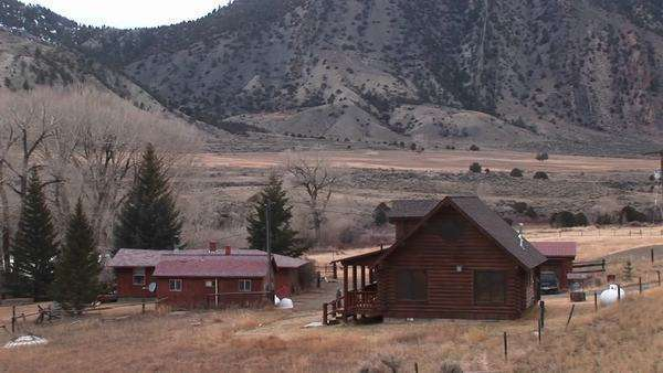 A rural homestead sits at the foot of a mountain range. Royalty-free stock video