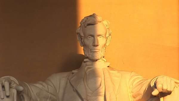 President Abraham Lincoln's sculpted face sits half in shadow and half bathed in golden light. Royalty-free stock video