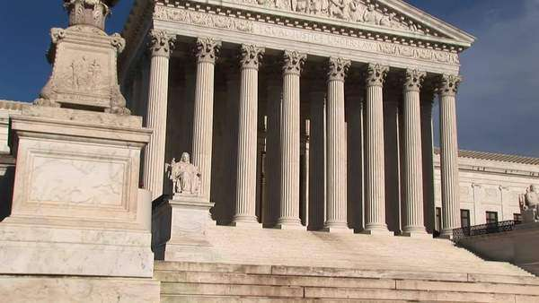 Warm sunlight shines on the white stone steps and bright white pillars of the U.S. Supreme Court Building entrance. Royalty-free stock video