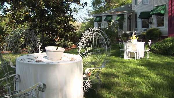 Whimsical tables and chairs furnish the yard of a Victorian home flanked by a bright red chimney. Royalty-free stock video