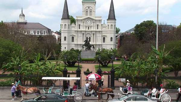Horse drawn carts and traffic pass by Jackson Square in the New Orleans French Quarter. Royalty-free stock video
