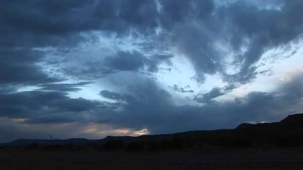 Pan-right shot of storm clouds over a hilly landscape. Royalty-free stock video