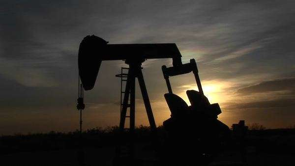 Medium shot of a silhouetted oil pump turning in the New Mexico desert. Royalty-free stock video