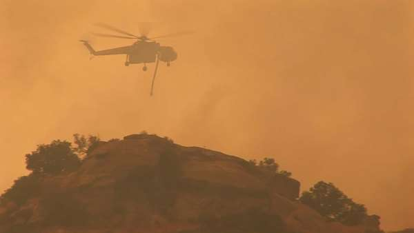 Following shot of a helicopter dropping chemicals on a wildfire in California. Royalty-free stock video