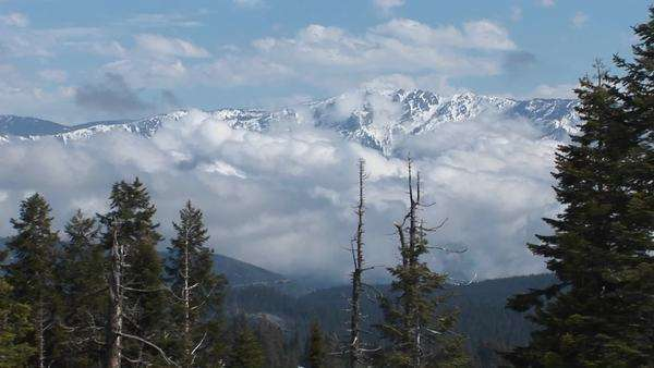 Wide shot of peaks covered with snow amongst clouds in Kings Canyon National Park. Royalty-free stock video