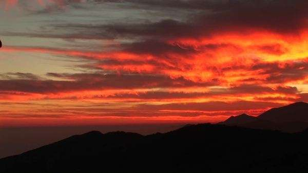 Medium-shot of a rock-climber silhouetted by a fiery California setting-sun. Royalty-free stock video