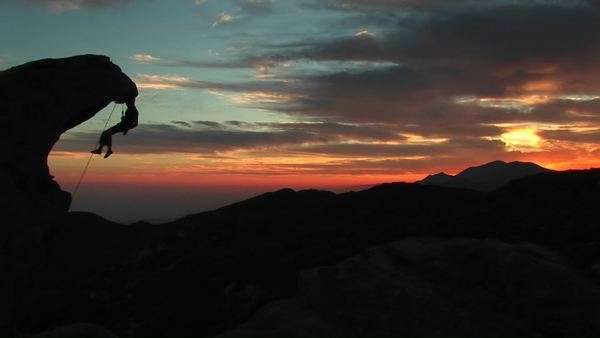 Medium-shot of a rock-climber silhouetted by the setting-sun hanging from an rock overhang. Royalty-free stock video