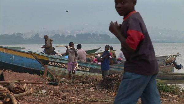 A group of children gather around fishing boats at Gaba Village on the shores of Lake Victoria. Royalty-free stock video