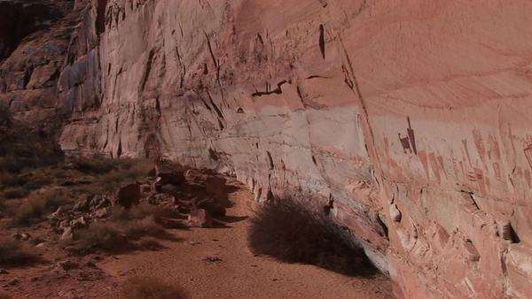 Pan-right slowly across the face of a remote canyon cliff with American Indian pictographs. Royalty-free stock video