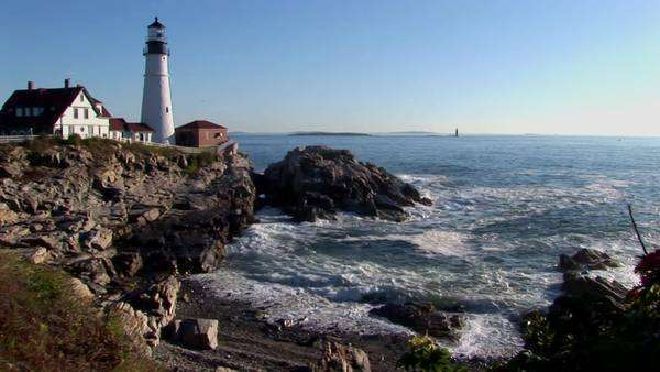 A lighthouse stands on a rocky shore. Royalty-free stock video