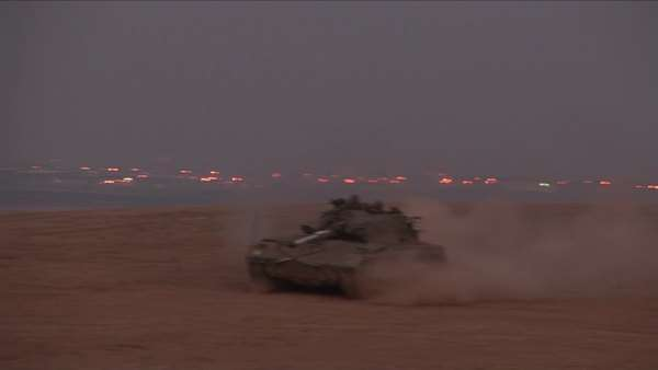 An Israeli tank moves across a no man's land between Israel and the Gaza Strip. Royalty-free stock video
