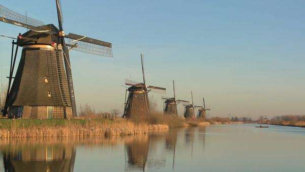 Windmills line up perfectly along a canal as a small boat crosses in the distance. Royalty-free stock video