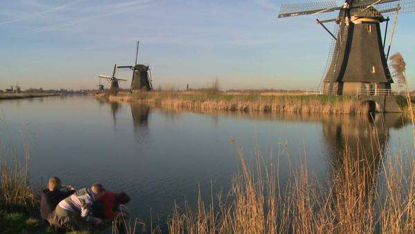 Children play in front of windmills along a canal in Holland. Royalty-free stock video