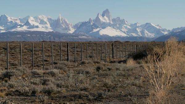 Pan across a fenced region in the far Southern region of Patagonia with the Fitzroy Range in background. Royalty-free stock video