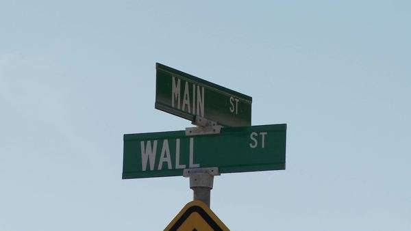 A street sign indicates the intersection of Main and Wall Streets. Royalty-free stock video