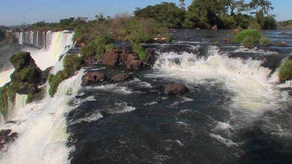 Pan across Iguacu Falls flowing out of the jungle with a rainbow foreground. Royalty-free stock video