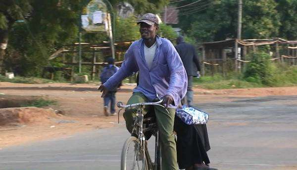 People ride bicycles and walk along a road in an African village. Royalty-free stock video