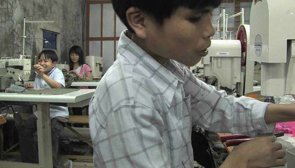 Asian youths sew in a factory. Royalty-free stock video