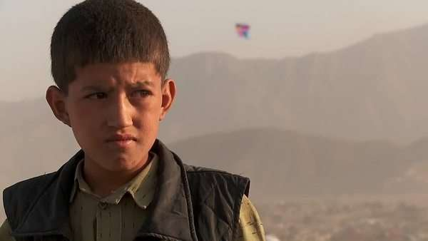 Close up portrait of boy's face as friends fly kites in an empty lot in Kabul, Afghanistan. Royalty-free stock video