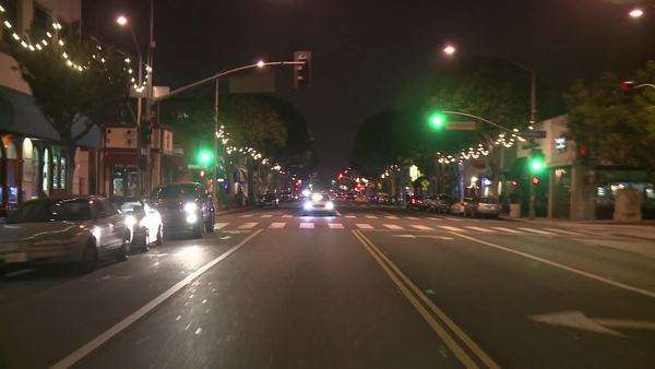 A vehicle drives through a city's festively decorated downtown. Royalty-free stock video