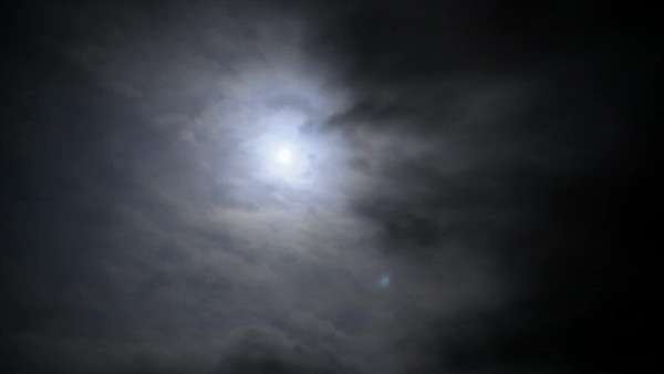 Timelapse clouds with the moon behind them in the night sky. Royalty-free stock video