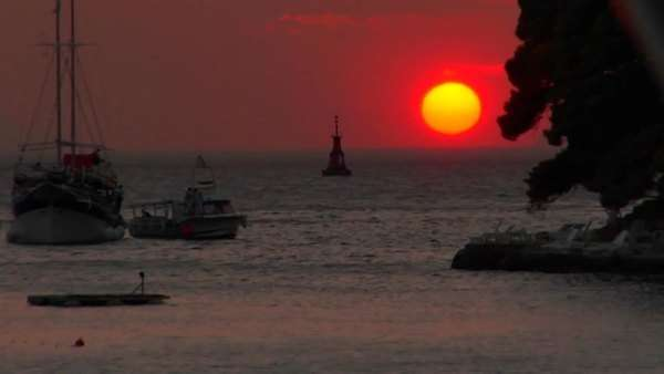 A Red setting Croatian sun sits just above the water at dusk. Royalty-free stock video